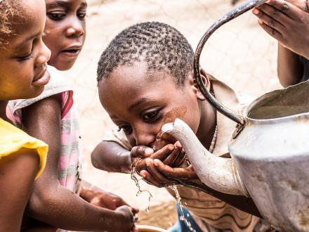 Suppenküche in Katutura, Namibia - Ein Kind trinkt Wasser aus einer Kanne