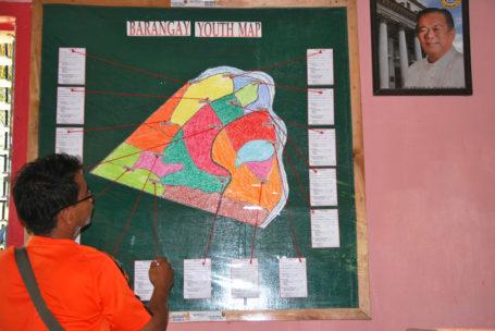 Ein Mann steht vor der Barangay youth Map